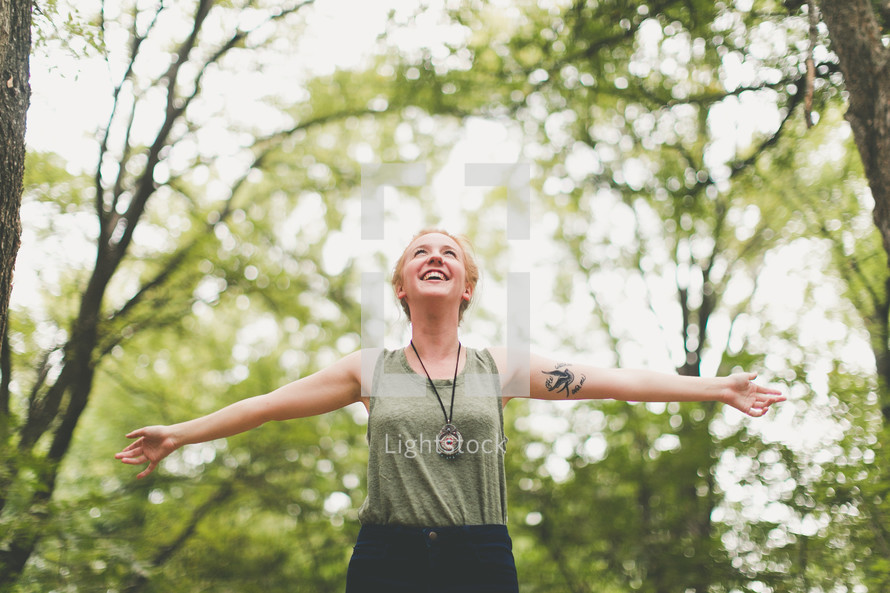 woman with open arms standing in a forest