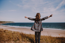 a girl standing on a shore with outstretched arms