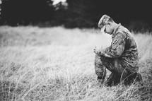 soldier kneeling in a field praying
