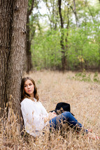 sitting, leaning against a tree, tree, outdoors, woman