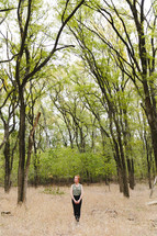woman standing outdoors alone in a forest