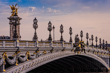 gold and marble bridge with ornate street lamps