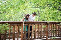 A young couple standing together at a bridge railing.
