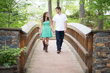 A young man and woman holding hands and walking over a bridge.