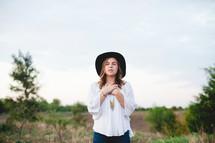 a woman standing outdoors praising God