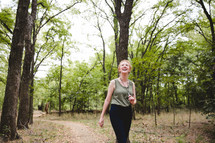 a woman walking on a trail through a forest