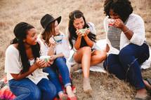 friends sitting on a beach drinking coffee