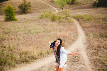 woman walking on a path with open arms