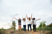 women with raised arms standing outdoors rejoicing