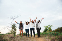 women standing outdoors with raised arms rejoicing