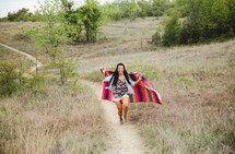 woman wrapped in a blanket walking up a hill