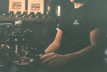 A barista makes a coffee with his hands