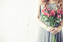 Pregnant woman holding bouquet of flowers.