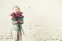 little boy holding a bouquet of flowers