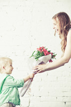 boy handing his mother a bouquet of flowers