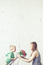 Son giving his mother a bouquet of flowers.