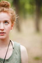 face, closeup, half face, half, red head, bun, standing, forest, trees, outdoors