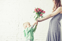 son handing his mother a bouquet of flowers