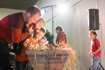 children placing flowers in a manger