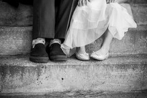 feet of a father and daughter sitting on steps