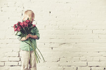 Boy hiding his face behind a bouquet of flowers standing in front of a brick wall.