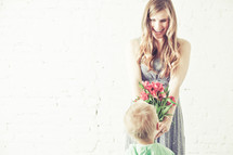 Son giving bouquet of flowers to his mother.