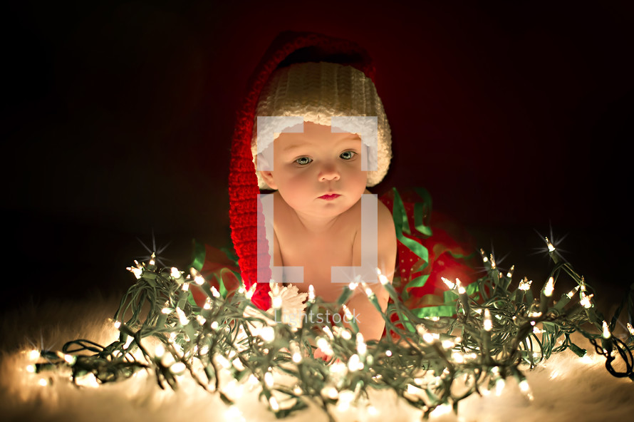 a baby in a santa hat and Christmas lights