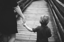Mother holding child's hand as they walk across a wooden bridge.