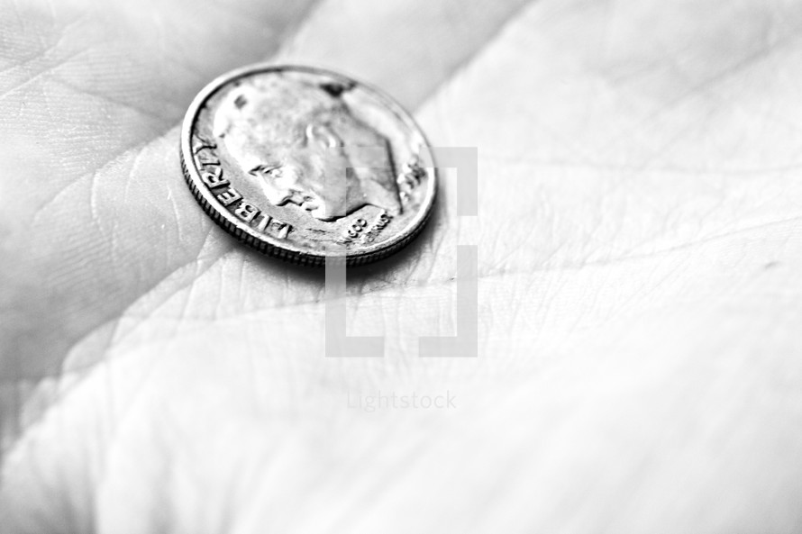 A dime rests in the palm of a hand
