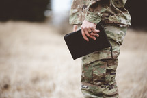 soldier holding a Bible at his side