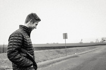 a man in a coat standing on the side of a road
