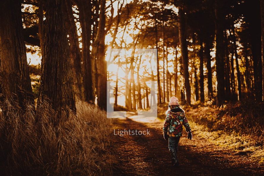 a child in a coat walking on a path in a forest