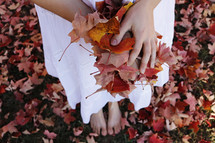barefoot woman holding fall leaves