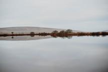 a hill behind a pond