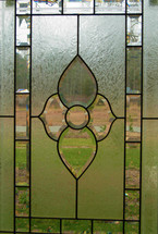 A cut glass window with stained glass pattern showing the outdoors and green grass peering through a cut glass window.