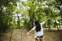 woman with open arms walking in a forest