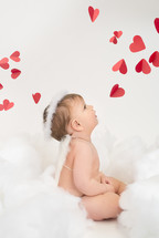 infant in angel wings and red hearts