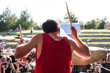 a man playing drums at an outdoor festival concert