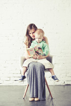 Mother holding son in her lap while sitting in a chair against a brick wall reading.