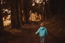 a toddler in a coat walking on a path in a forest