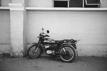 motorcycle leaning against a wall