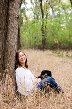 woman sitting leaning against a tree outdoors