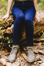 woman's legs and shoes as she sat on a log