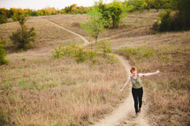 woman walking on a path up a hill with open arms
