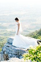 a bride standing at the edge of a cliff