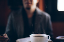steam rising from a coffee mug in front of a man