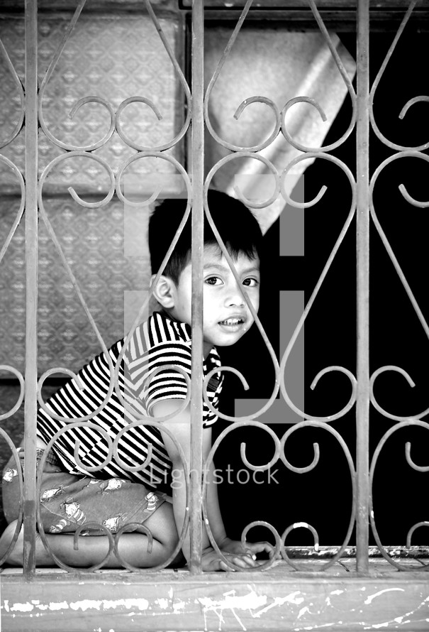 Child playing behind iron window