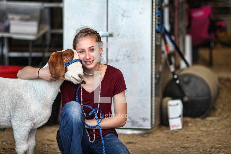 Country girl smiles contentedly with the goat she has raised and loves.