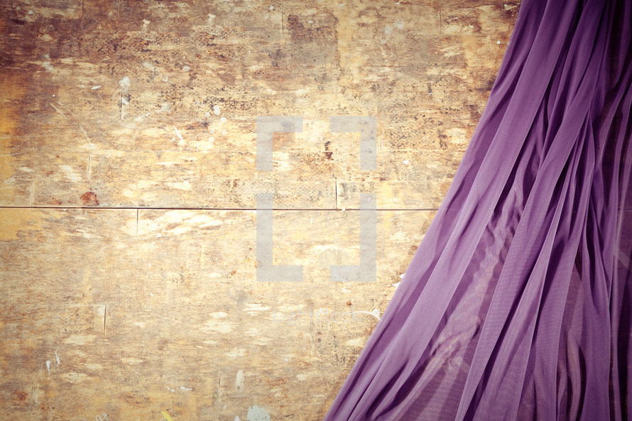 Purple drape against plywood.