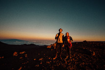 a couple holding hands standing on a mountaintop at sunrise